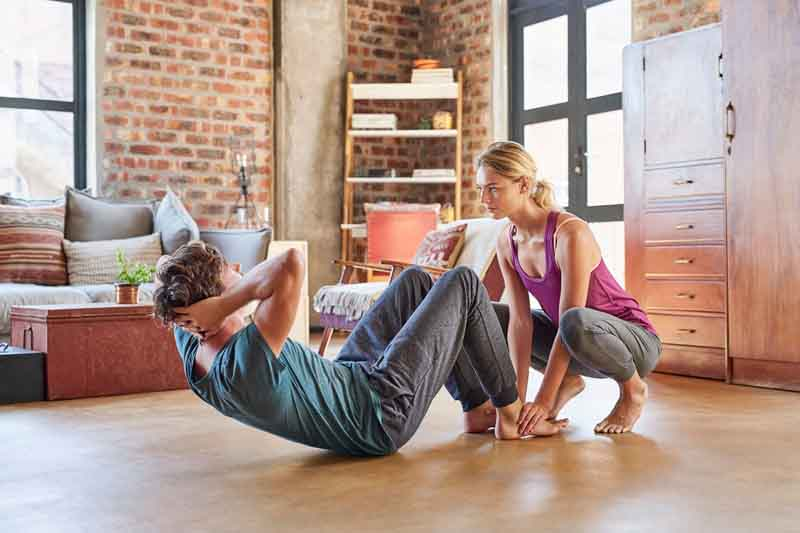 Woman assisting man in doing sit-ups at home